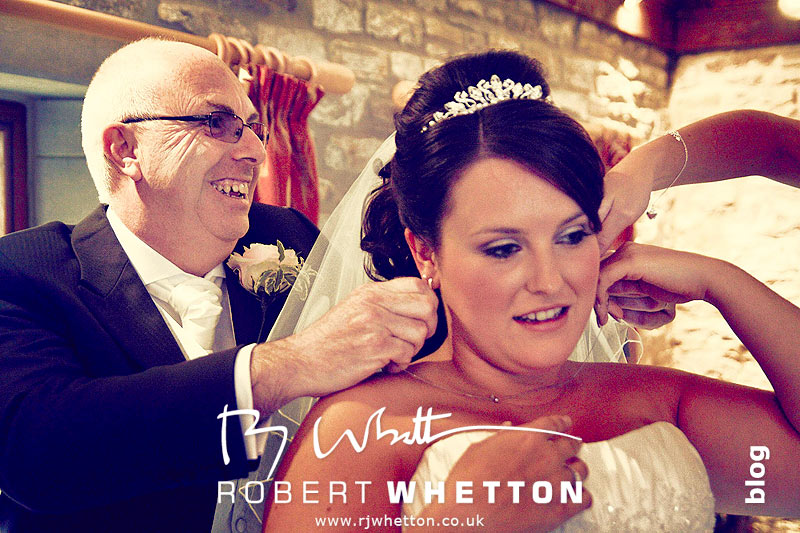 Jo's dad putting on her necklace - Dorset Wedding Photographer Robert Whetton
