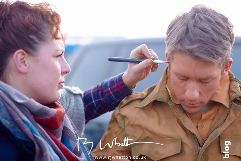 Rosie Lee adds final make-up to orange army man - Production Photography Dorset