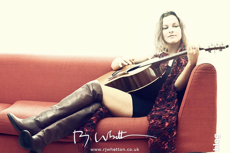 Kirstin Topol playing guitar on sofa