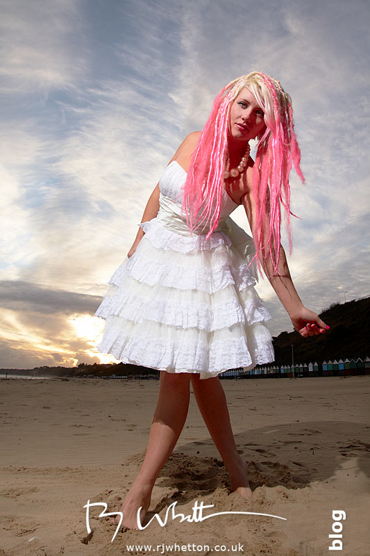 Pixie poses on the beach against the settnig sun - Professional Portraits Dorset