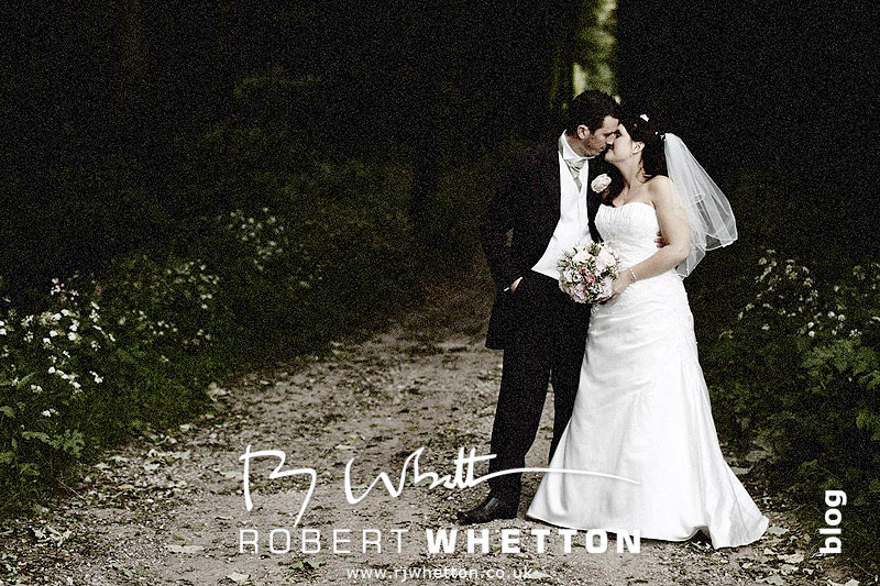 Jo and Ben kissing under the trees - Dorset Wedding Photographer Robert Whetton