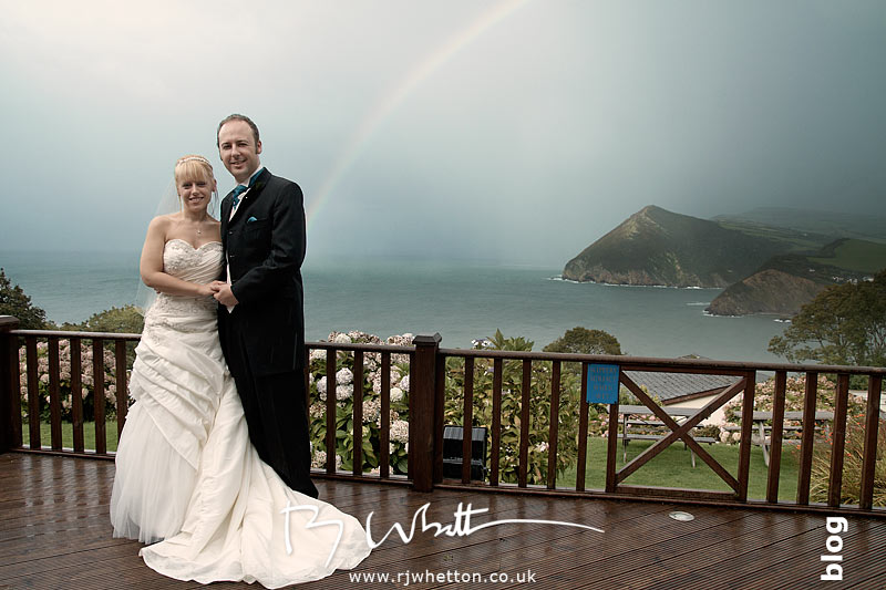 North Devon Wedding with Matt Fryer -Lynsey and Ash on the balcony with a rainbow in-between the rain