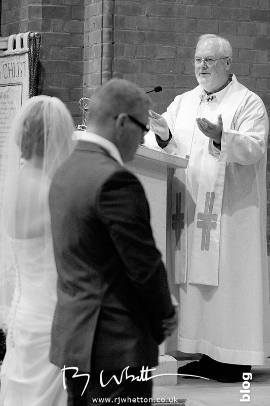 Father Denis giving the married couple some advice - Professional Wedding Photography Dorset