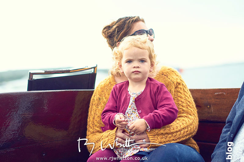 Harper sitting on mums lap in the boat - Portrait Photography Dorset