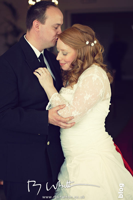 Anna and Nick embracing after giving of rings - Wedding Photography Dorset