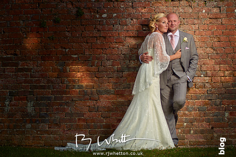 Sharon and Greg posing in front of an old wall at The East Close Hotel, Dorset - Wedding Photography Dorset