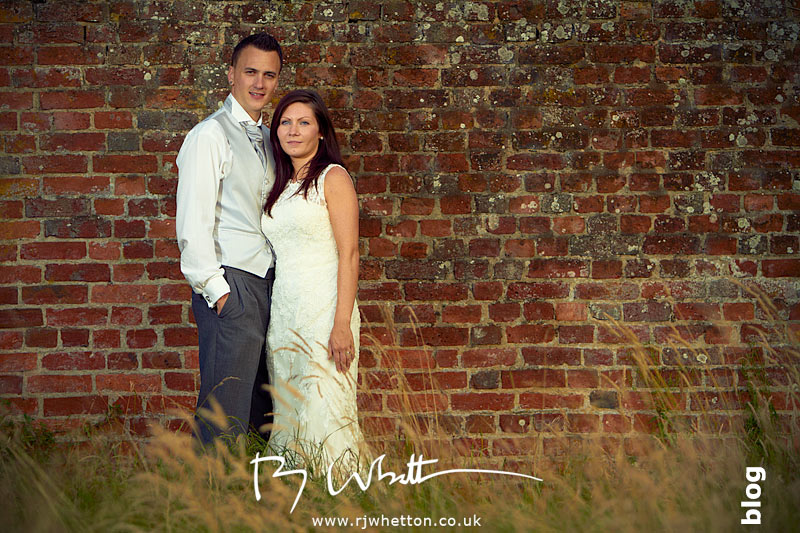 Stacy and Darren posing in front of an old wall in Christchurch, Dorset - Wedding Photography Dorset
